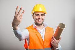Portrait of young architect holding blueprints showing number th. Ree and smiling on gray background Royalty Free Stock Photos