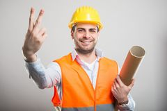 Portrait of young architect holding blueprints showing number tw. O and smiling on gray background Royalty Free Stock Images