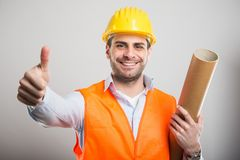 Portrait of young architect holding blueprints showing thumb up. Gesture and smiling on gray background Royalty Free Stock Photography