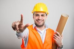Portrait of young architect holding blueprints showing two finge. Rs and smiling on gray background Stock Photos
