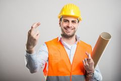 Portrait of young architect holding fingers crossed. Portrait of young architect wearing hardhat holding fingers crossed and smiling on gray background Stock Photos