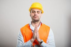 Portrait of young architect holding hands together like praying. On gray background stock photo