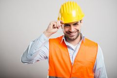 Portrait of young architect holding his helmet like salute. And smiling on gray background Royalty Free Stock Photo