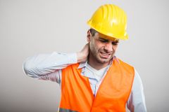 Portrait of young architect holding neck like in pain. On gray background stock image
