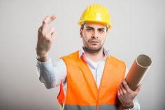 Portrait of young architect holding fingers crossed. Portrait of young architect wearing hardhat holding fingers crossed on gray background Royalty Free Stock Photos