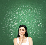 A portrait of a young artful brunette lady who is thinking about advantages of education. The lady is in a white tank top. Educati Stock Image
