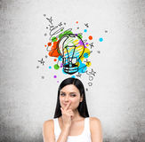 A portrait of a young artful brunette lady who is trying to create a new idea for some business project or case study. A colourful. Lightbulb as a concept of a Royalty Free Stock Images
