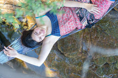 Portrait of young Asia beautiful girl relaxing on hammock on the Stock Photo