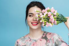 Portrait of young Asia woman play with bouquet in blue background royalty free stock image