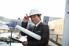 Portrait of young asian architect. Young architect with white helmet holding blueprint and clipboard smiling look at the camera Stock Photos