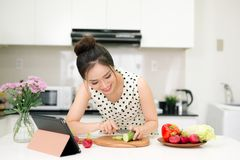 Portrait of young asian beautiful woman cooking in kitchen.  Royalty Free Stock Image