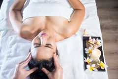 Oil head spa massage to woman. Portrait of young Asian beautiful woman in spa club. Body care treatment by Thai oil. Cute girl having massage at head by royalty free stock images