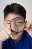 Portrait of a young asian child looking through a magnifying gla Royalty Free Stock Images