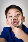 Portrait of a young asian child looking through a magnifying gla Stock Photography