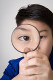 Portrait of a young asian child looking through a magnifying gla Stock Photos