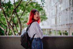 Portrait of young Asian fashionista girl student with red hair royalty free stock photo