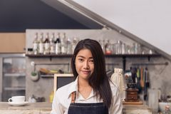Portrait of young Asian female barista smiling to welcome her customer to coffee shop with a background of beverage bar counter. Young female barista smile in Stock Images