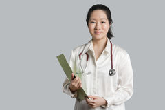 Portrait of a young Asian female doctor with a clipboard over gray background Royalty Free Stock Images