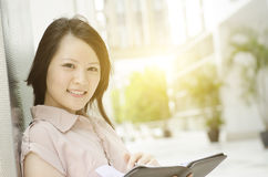 Portrait of young Asian female executive. Young Asian woman executive smiling and standing at an office environment, natural golden sun light at background Royalty Free Stock Images