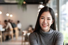 Young asian female in cafe. A portrait of a young Asian female smiling inside a cafe or restaurant interior royalty free stock image