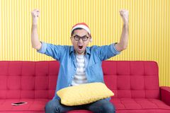 Young man with denim shirt. Portrait of young Asian handsome bearded man, wearing eyeglasses, Santa hat, in denim shirt, sitting on red sofa, wide eyes, clench royalty free stock photos