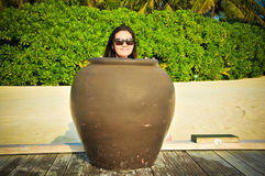 Portrait of young asian looking woman hiding behind pot tropical beach at Maldives Stock Photos