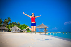 Portrait of young asian looking woman jumping happy at beautiful tropical beach at Maldives Royalty Free Stock Photography