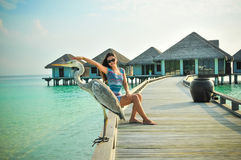 Portrait of young asian looking woman pretending touching a bird at tropical beach at Maldives Royalty Free Stock Photos