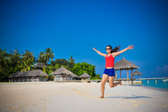 Portrait of young asian looking woman rising up hands at beautiful tropical beach at Maldives Royalty Free Stock Image