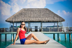 Portrait of young asian looking woman sitting near restaurant at beautiful tropical beach at Maldives Stock Photo