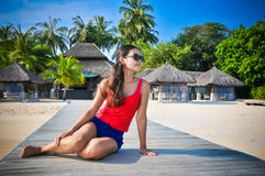 Portrait of young asian looking woman sitting near restaurant at beautiful tropical beach at Maldives Royalty Free Stock Photos