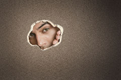 Portrait of a young Asian male peeking from paper hole Stock Photos