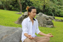 Portrait of young Asian man doing yoga meditation while sitting in lotus position on the rock in beautiful outdoor park. Stock Photography