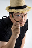 Portrait of a young asian man looking through a magnifying glass Stock Image