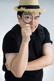 Portrait of a young asian man looking through a magnifying glass Stock Photos