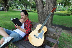 Portrait of young asian man in red shirt reading a book on the bench against in beautiful outdoor park. Royalty Free Stock Photos