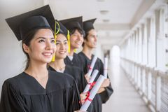 Portrait of young asian man and woman graduates standing in line royalty free stock images