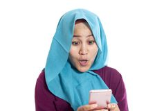 Portrait of young Asian muslim woman get good news on her phone, happy surprised expression royalty free stock photography