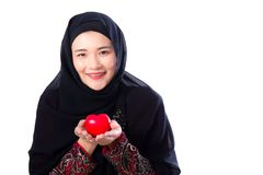 Portrait of young asian muslim woman holding red heart shaped pillow isolated Stock Images