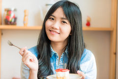 Portrait of young asian pretty smiling woman eating cake at cafe Royalty Free Stock Photo