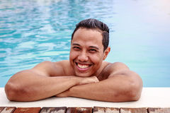 Portrait of young Asian smiling man relaxing in swimming pool, s. Ummer outdoor concept Stock Images