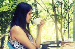 Portrait young asian woman drinking hot green tea latte in coffe. E shop Stock Photo