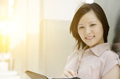 Portrait of young Asian woman executive. Young Asian woman executive smiling and standing at an office environment, natural golden sunlight at background Stock Image