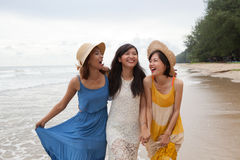 portrait of young asian woman with happiness emotion wearing beautiful dress walking on sea beach and laughing joyful use for stock images