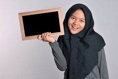 Portrait of young asian woman in islamic headscarf holding chalkboard. Smiling asian woman wearing  islamic headscarf holding stock photo
