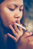 Portrait of young Asian woman lighting up the cigarette Stock Photos