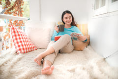 Portrait of young asian woman reading book at home Stock Photography