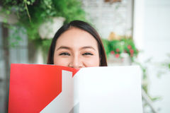 Portrait of young asian woman reading book at home Royalty Free Stock Photos