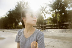 Portrait of young asian woman sitting at beach.vacation time concept.blurred background.sunset moment.flare from the sun royalty free stock photo
