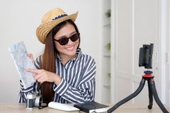 Portrait of young asian woman travel blogger holding map while r. Ecording video, live streaming, on social media, blogger and vlogger concept royalty free stock image